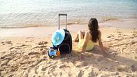 Beautiful woman sitting with a suitcase on a sunny beach