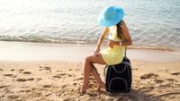 Frau breitet Sonnenschutzmittel auf ihren Beinen aus