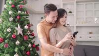 Asiatiska par som tar selfies med julgranen