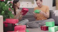 Asiatische Paare, die Weihnachtsgeschenke einwickeln