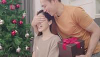 Asian couple exchanging Christmas gifts