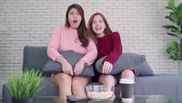 Jeunes femmes regardent la télé et rient
