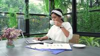 Junge asiatische Frau, die an Laptop arbeitet