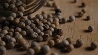 Granos de pimienta sobre mesa de madera