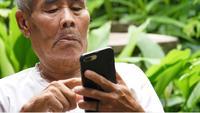 Äldre man som sveper på sin smartphone