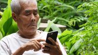 Elderly man swiping on his smartphone