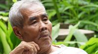 Älterer Mann, der alleine im Park spricht