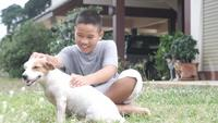 Junge, der mit seinem Hund sitzt auf dem Gras spielt
