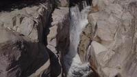 Drone descendo para uma cachoeira em um dia ensolarado de verão na Córsega