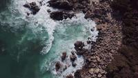 Drone voando sobre uma praia com ondas em 4K