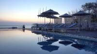 Buitenzwembad met uitzicht op zee bij zonsondergang