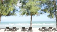 Paraplu en stoel op het strand