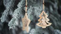 Juguetes navideños de madera colgando de las ramas de un árbol de navidad