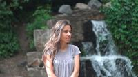 Young Woman Posing With A Waterfall As A Background.