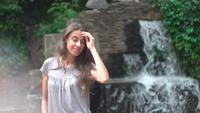 Jovem posando com uma cachoeira como pano de fundo.