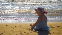 Little Girl Sitting On The Sand By The Sea