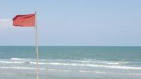 Drapeau rouge flottant à la plage
