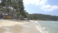 Gente caminando en la arena de una playa tropical