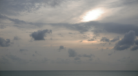 Solnedgång bak molnen och över havet