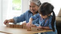 Oma en kleindochter spelen met Jenga-blokken
