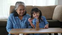 Grand-mère et petite-fille jouent avec des blocs de Jenga