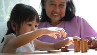 Mormor och barnbarn lekte med Jenga-block