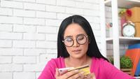 Vrouw die het Aantal van een Creditcard op een Telefoon typt