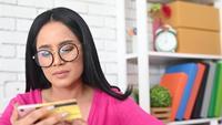 Femme taper le numéro d'une carte de crédit sur un téléphone