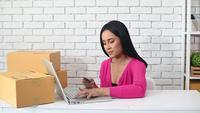 Kvinna som skriver antalet kreditkort på en bärbar dator