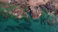 Drone vliegt links over een rotsachtige kust
