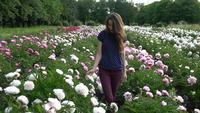 Jonge Vrouw die op een Gebied van Pioenen loopt