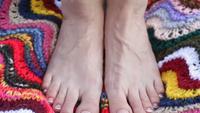 Os pés da mulher em um cobertor de matéria têxtil