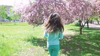Mulher feliz correndo no jardim primavera florescendo