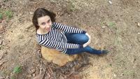 Kvinna sitter på en stubbe