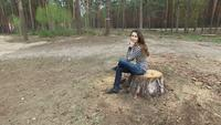Woman Sits On A Stump