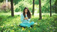Femme avec téléphone assis sur l'herbe