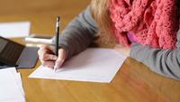 Ung kvinna som skriver på ett pappersark