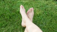 Kvinnas fötter på gräset