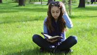 Jovem mulher lendo no parque