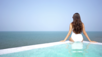 Ung kvinna som kopplar av i en simbassäng