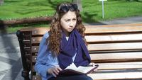 Young Woman Reads Sitting In The Park