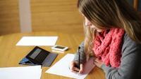 Jeune femme écrivant sur une feuille de papier