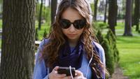 Jeune femme écoutant de la musique dans le parc