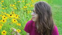 Mujer joven que huele a flores amarillas