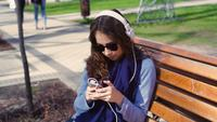 Young Woman Listening To Music In The Park