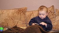 Barn som leker med mobiltelefonen på soffan
