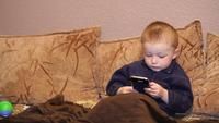 Niño jugando con teléfono móvil en el sofá
