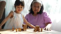 Mormor och barnbarn spelar med Jenga-block
