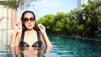 Mujer joven que se relaja en una piscina