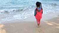 Asiatisches kleines Mädchen, das auf dem Strand spielt